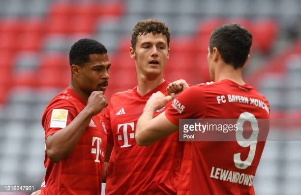 Robert Lewandowski of Bayern Munich celebrates with Serge Gnabry and Benjamin Pavard after their team's first goal came through a own goal during the...