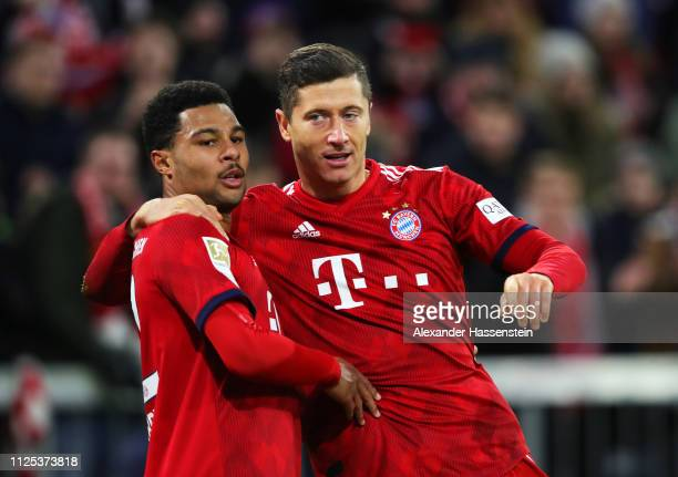 Robert Lewandowski of Bayern Munich celebrates with Serge Gnabry as he scores his team's fourth goal during the Bundesliga match between FC Bayern...
