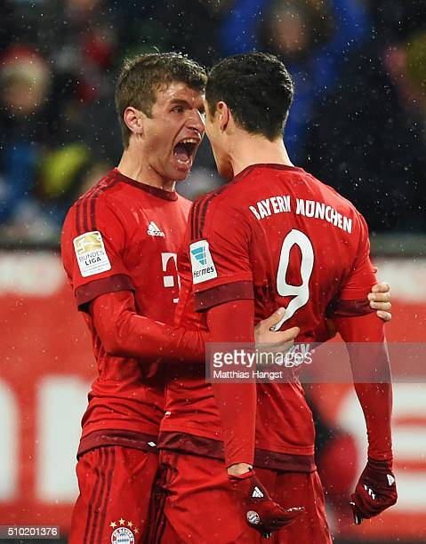 Robert Lewandowski of Bayern Munich celebrates with Thomas Mueller as he scores their first goal during the Bundesliga match between FC Augsburg and...