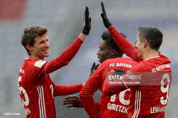 Robert Lewandowski of Bayern Munich celebrates with Thomas Mueller after scoring their team's first goal during the Bundesliga match between FC...