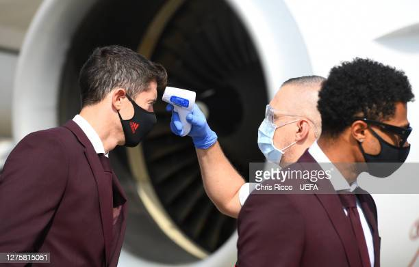 Robert Lewandowski of Bayern Munich has his temperature checked after exiting the team plane as the Bayern Munich team arrive in Budapest ahead of...