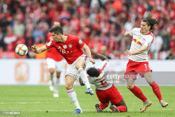 Robert Lewandowski of Bayern Munich Ibrahima Konate of RB Leipzig and Marcel Sabitzer of RB Leipzig battle for possession during the DFB Cup final...