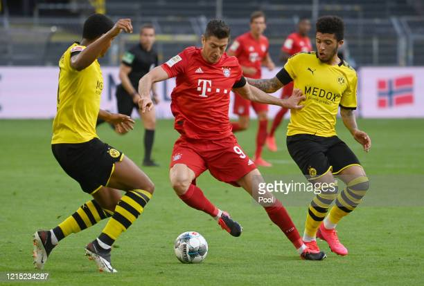 Robert Lewandowski of Bayern Munich is challenged by Jadon Sancho and Manuel Akanji of Borussia Dortmund during the Bundesliga match between Borussia...