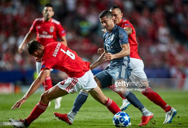 Robert Lewandowski of Bayern Munich is challenged by Ljubomir Fejsa and Ruben Dias of Benfica during the Group E match of the UEFA Champions League...
