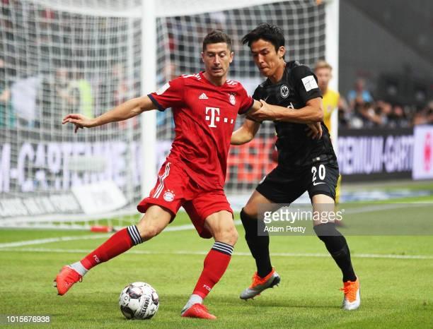 Robert Lewandowski of Bayern Munich is challenged by Makoto Hasebe of Eintracht Frankfurt during the DFL Supercup 2018 match between Eintracht...