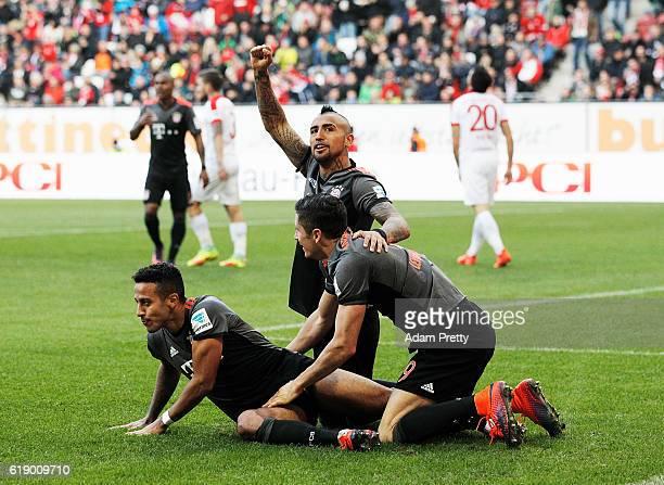 Robert Lewandowski of Bayern Munich is congratulated by Thiago Alcantara and Arturo Vidal after scoring the third goal during the Bundesliga match...