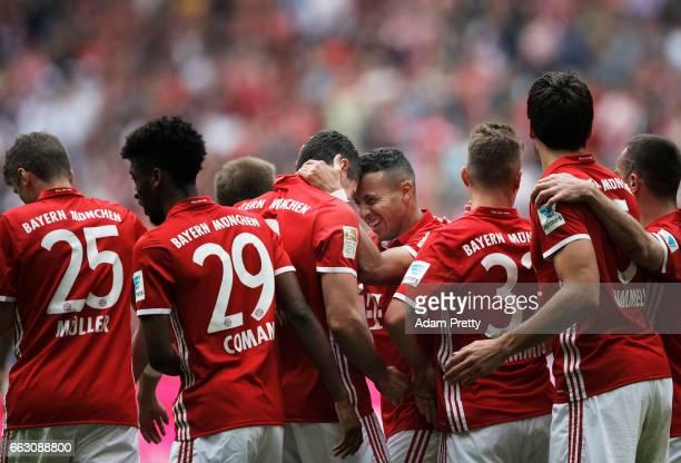 Robert Lewandowski of Bayern Munich is congratulated by Thiago Alcantara of Bayern Munich after scoring his third goal during the Bundesliga match...