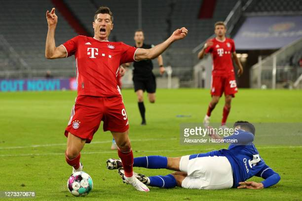 Robert Lewandowski of Bayern Munich is tackled and fouled for a penalty by Ozan Kabak of Schalke 04 during the Bundesliga match between FC Bayern...
