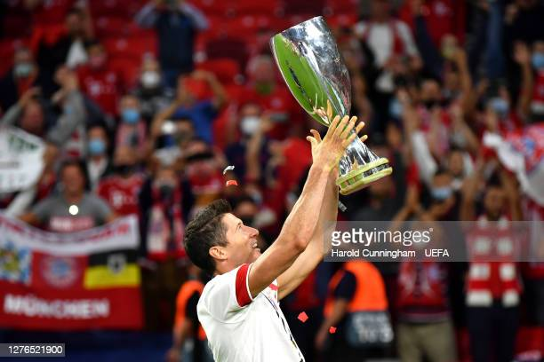 Robert Lewandowski of Bayern Munich lifts the UEFA Super Cup trophy as he celebrates victory over FC Sevilla at Puskas Arena on September 24, 2020 in...