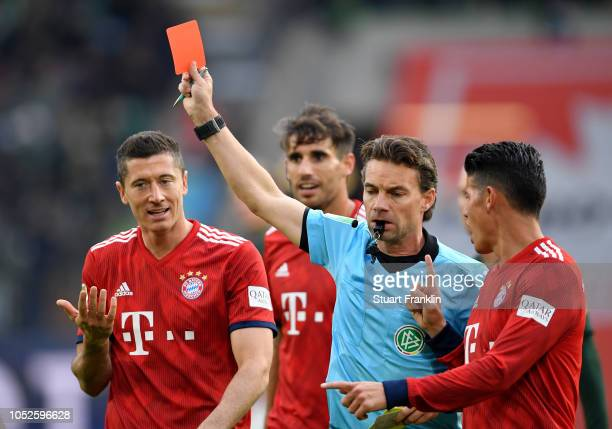 Robert Lewandowski of Bayern Munich protests to referee Guido Winkmann as he shows Arjen Robben of Bayern Munich a red card during the Bundesliga...