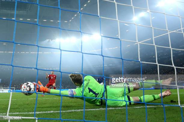 Robert Lewandowski of Bayern Munich scores a penalty for his team's second goal past Ralf Faehrmann of FC Schalke 04 during the Bundesliga match...