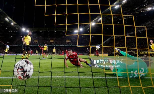 Robert Lewandowski of Bayern Munich scores his team's first goal during the Bundesliga match between Borussia Dortmund and FC Bayern Muenchen at...