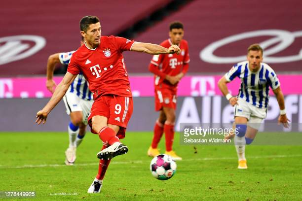 Robert Lewandowski of Bayern Munich scores his team's fourth goal from the penalty spot to complete his hat-trick during the Bundesliga match between...