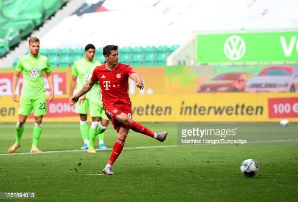 Robert Lewandowski of Bayern Munich scores his team's third goal from the penalty spot during the Bundesliga match between VfL Wolfsburg and FC...