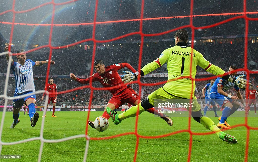 Robert Lewandowski of Bayern Munich (C) scores their first goal past goalkeeper Oliver Baumann of Hoffenheim during the Bundesliga match between FC Bayern Muenchen and 1899 Hoffenheim at Allianz Arena on January 31, 2016 in Munich, Germany.