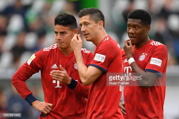 Robert Lewandowski of Bayern Munich speaks to James Rodriguez of Bayern Munich and David Alaba of Bayern Munich during the Bundesliga match between...