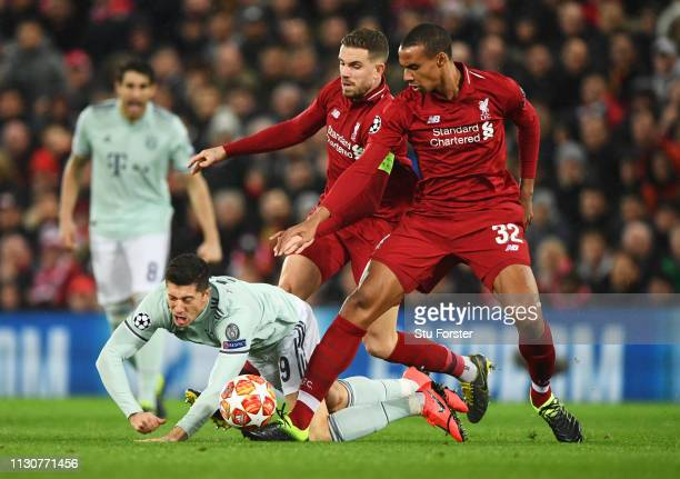 Robert Lewandowski of Bayern Munich tangles with Joel Matip and Jordan Henderson of Liverpool during the UEFA Champions League Round of 16 First Leg...