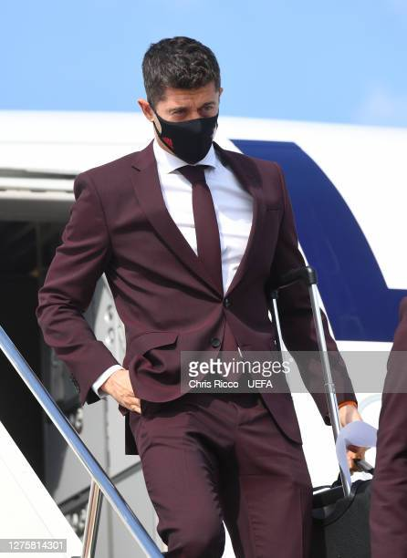 Robert Lewandowski of Bayern Munich walks off the team plane wearing a face mask as the Bayern Munich team arrive in Budapest ahead of the UEFA Super...