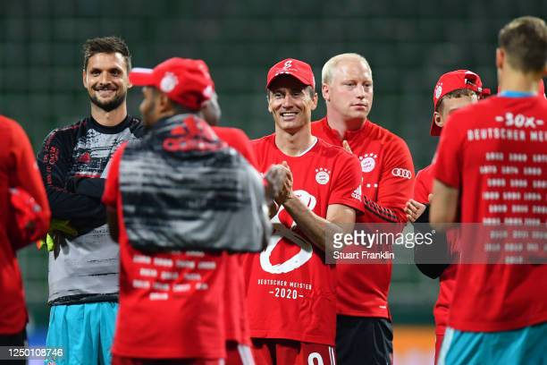 Robert Lewandowski of Bayern Munich wears a shirt and cap in celebration of securing the Bundesliga title following their victory in the Bundesliga...