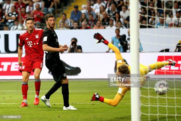 Robert Lewandowski of Bayern scores the first goal against Frederik Roennow of Frankfurt during the DFL Supercup match between Eintracht Frankfurt an...