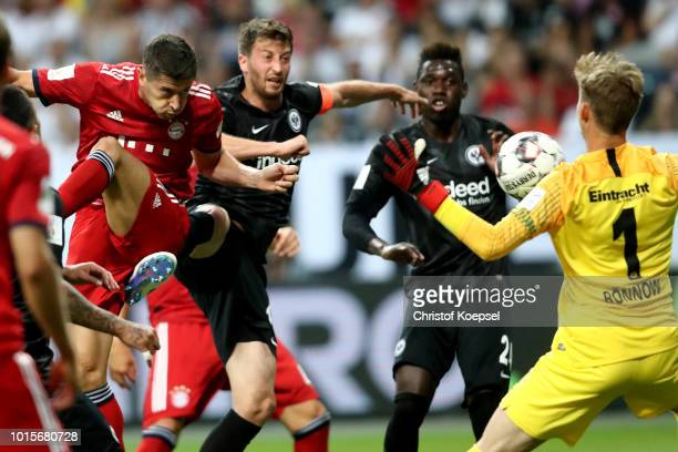 Robert Lewandowski of Bayern scores the second goal against David Abraham and Frederik Roennow of Frankfurt during the DFL Supercup match between...