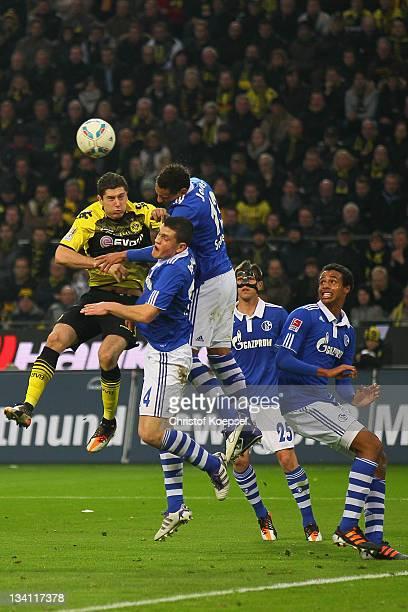 Robert Lewandowski of Dormtund Kyriakos Papadopoulos and Jermaine Jones of Schalke go up for a header during the Bundesliga match between Borussia...