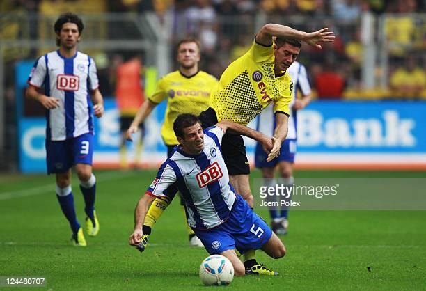 Robert Lewandowski of Dortmund and Andre Mijatovic of Berlin battle for the ball during the Bundesliga match between Borussia Dortmund and Hertha BSC...