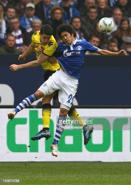 Robert Lewandowski of Dortmund and Atsuto Uchida of Schalke go up for a header during the Bundesliga match between FC Schalke 04 and Borussia...