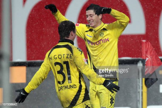 Robert Lewandowski of Dortmund celebrates his team's second goal with team mate Mario Goetze during the Bundesliga match between 1 FC Nuernberg and...