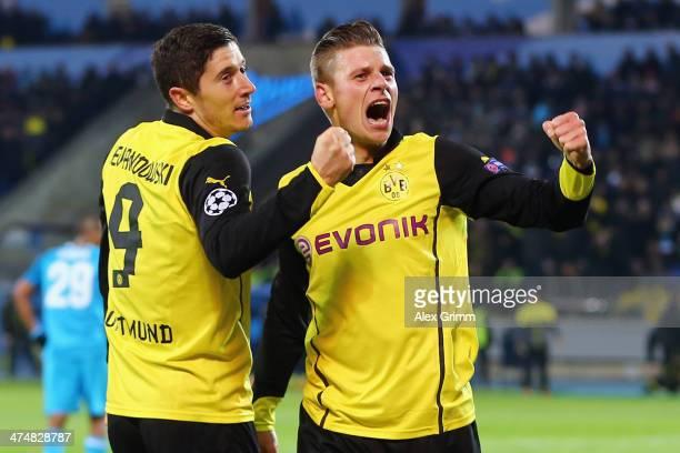 Robert Lewandowski of Dortmund celebrates his team's third goal with team mate Lukas Piszczek during the UEFA Champions League Round of 16 match...