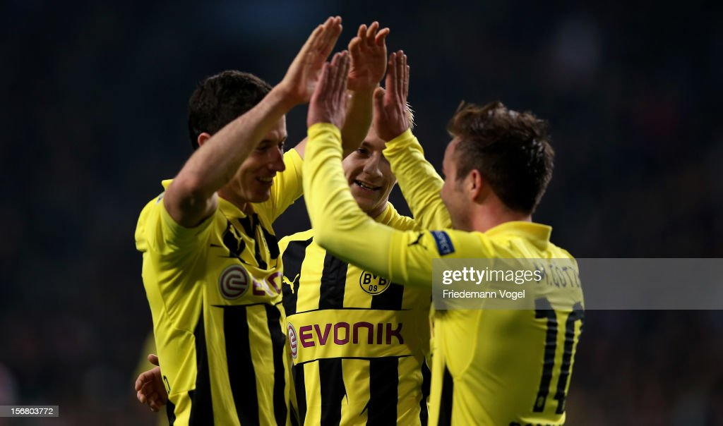 Robert Lewandowski of Dortmund celebrates scoring the fourth goal with Marco Reuss and Mario Goetze during the UEFA Champions League Group D match between Ajax Amsterdam and Borussia Dortmund at Amsterdam Arena on November 21, 2012 in Amsterdam, Netherlands.