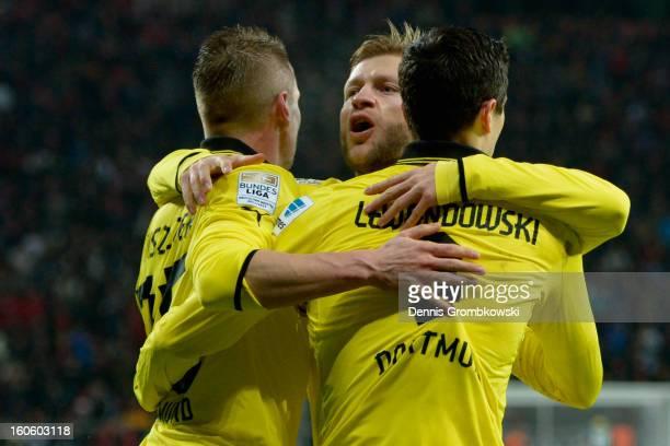 Robert Lewandowski of Dortmund celebrates with teammates Lukasz Piszczek and Jakub Blaszczykowski during the Bundesliga match between Bayer 04...