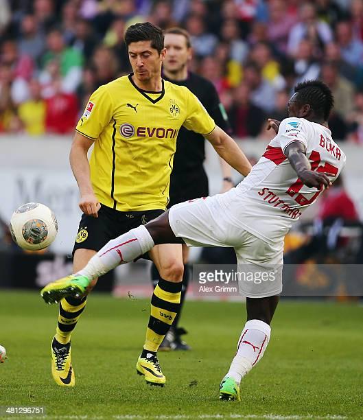 Robert Lewandowski of Dortmund is challenged by Arthur Boka of Stuttgart during the Bundesliga match between VfB Stuttgart and Borussia Dortmund at...