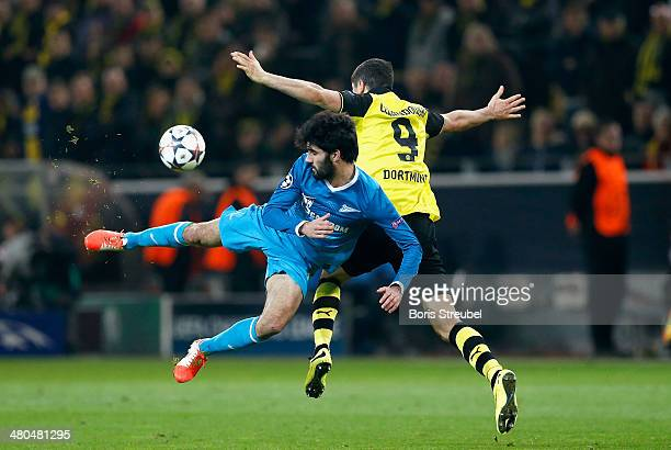 Robert Lewandowski of Dortmund is challenged by Luis Neto of Petersburg during the UEFA Champions League round of 16 second leg match between...