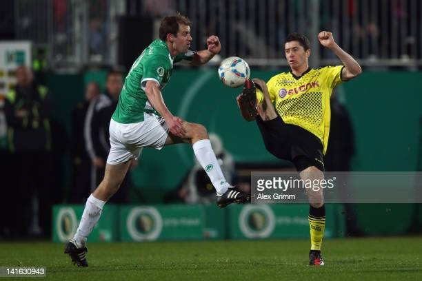 Robert Lewandowski of Dortmund is challenged by Thomas Kleine of Greuther Fuerth during the DFB Cup semi final match between SpVgg Greuther Fuerth...