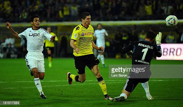 Robert Lewandowski of Dortmund scores his teams fourth goal past Josue and goalkeeper Diego Benaglio of Wolfsburg during the Bundesliga match between...