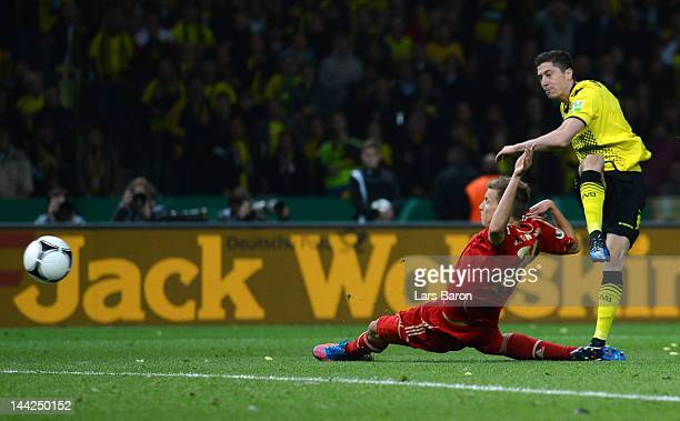 Robert Lewandowski of Dortmund scores his teams fourth goal past Holger Badstuber of Muenchen during the DFB Cup final match between Borussia...