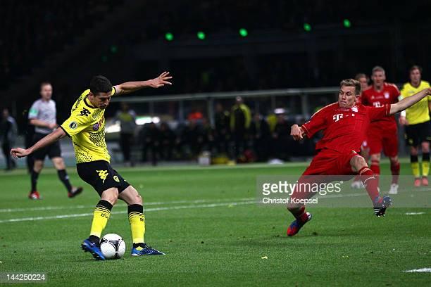 Robert Lewandowski of Dortmund scores the forth goal against Holger Badstuber of Bayern during the DFB Cup final match between Borussia Dortmund and...