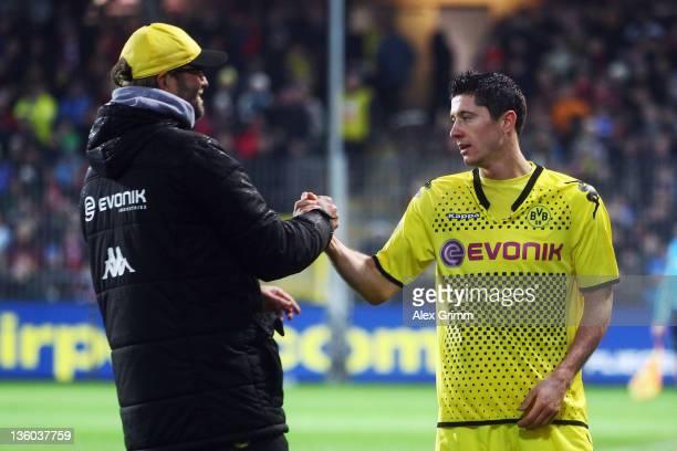 Robert Lewandowski of Dortmund shakes hands with head coach Juergen Klopp after being substituted during the Bundesliga match between SC Freiburg and...