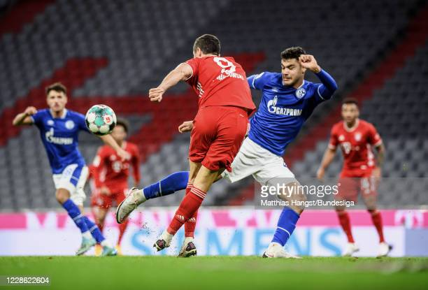 Robert Lewandowski of FC Bayern München provides an assist against Ozan Kabak of Schalke during the Bundesliga match between FC Bayern München and FC...
