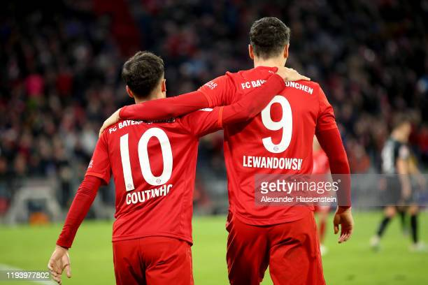Robert Lewandowski of FC Bayern Muenchen and teammate Philippe Coutinho celebrate after their sides fourth goal during the Bundesliga match between...