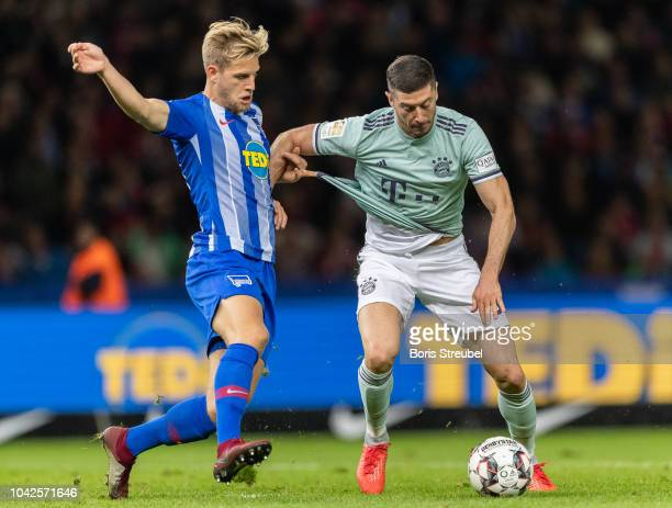 Robert Lewandowski of FC Bayern Muenchen battles for the ball with Arne Maier of Hertha BSC during the Bundesliga match between Hertha BSC and FC...