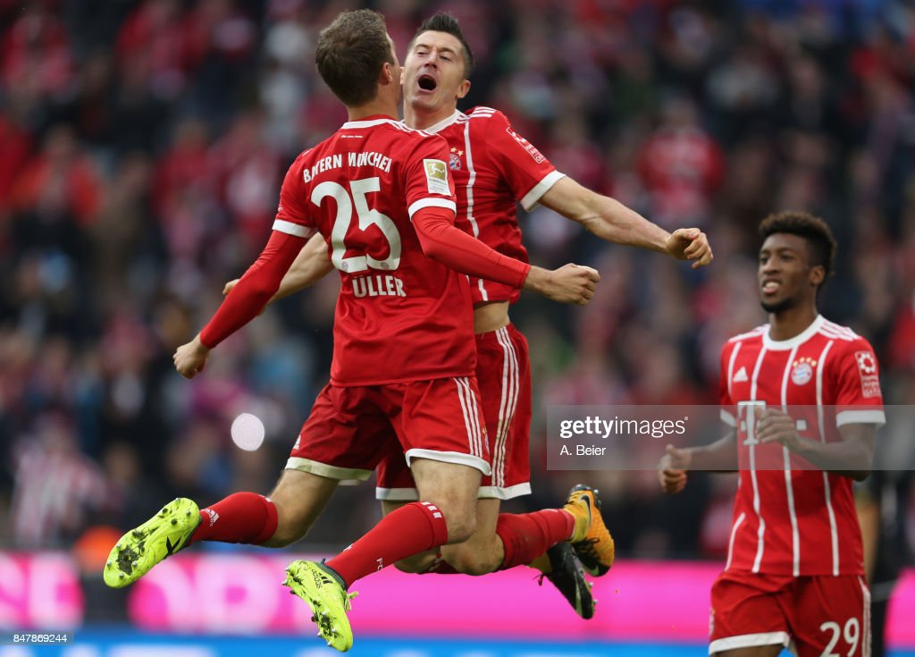 Robert Lewandowski (C) of FC Bayern Muenchen celebrates his first goal with teammate Thomas Mueller (L) during the Bundesliga match between FC Bayern Muenchen and 1. FSV Mainz 05 at Allianz Arena on September 16, 2017 in Munich, Germany.