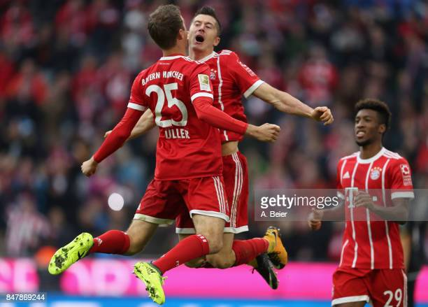 Robert Lewandowski of FC Bayern Muenchen celebrates his first goal with teammate Thomas Mueller during the Bundesliga match between FC Bayern...