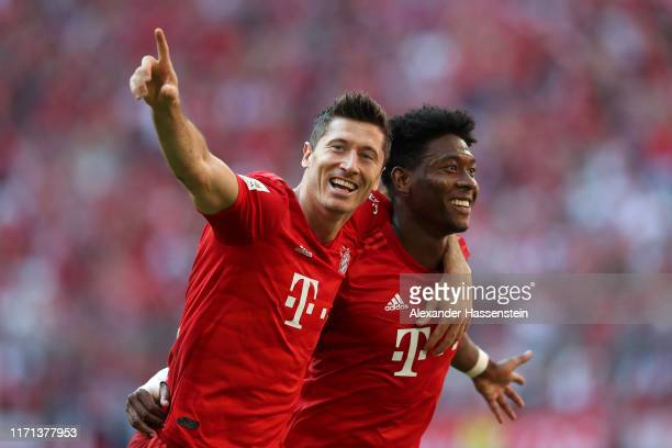 Robert Lewandowski of FC Bayern Muenchen celebrates scoring the 5th goal with his team mate David Alaba during the Bundesliga match between FC Bayern...