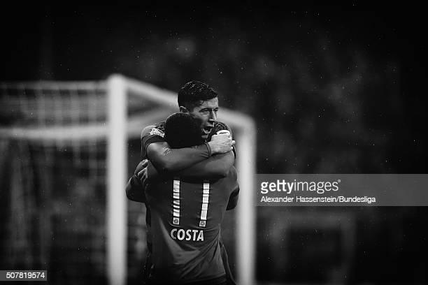 Robert Lewandowski of FC Bayern Muenchen celebrates scoring the opening goal with his team mate Douglas Costa during the Bundesliga match between FC...