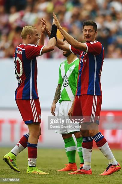 Robert Lewandowski of FC Bayern Muenchen celebrates with team mate Sebastian Rode after scoring his team's third goal during the Telekom Cup 2014...