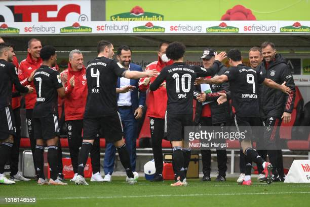 Robert Lewandowski of FC Bayern Muenchen celebrates with team mates and coaching staff after scoring their side's first goal from the penalty spot...