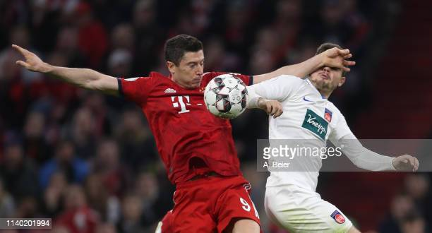 Robert Lewandowski of FC Bayern Muenchen fights for the ball with Marnon Busch of 1. FC Heidenheim doing a hand ball during the DFB Cup quarter final...