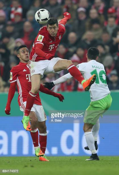 Robert Lewandowski of FC Bayern Muenchen fights for the ball with Yunus Malli of VfL Wolfsburg next to Thiago of Bayern Muenchen during the DFB Cup...